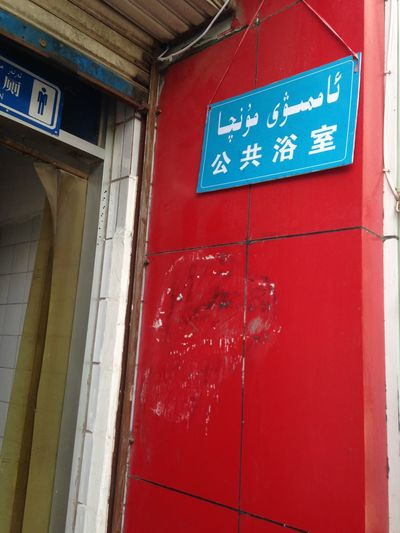 An entrance of public bath in Kucha, Xinjiang, China. Arabic Alphabet Entrance Architecture Building Exterior Built Structure Chinese Characters Close-up Day No People Outdoors Public Bath Public Bathhouse Public Baths Red Text Uyghur