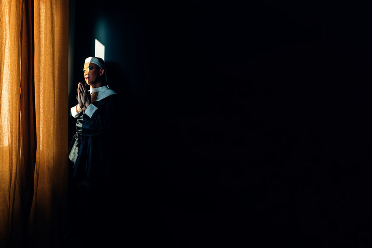 Devoted nun prays in the light of a convent window. cross dressing drag queen, religion, identity.