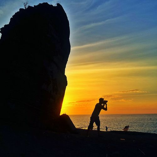 Silhouette Man At Beach By Sea Against Sky During Sunset