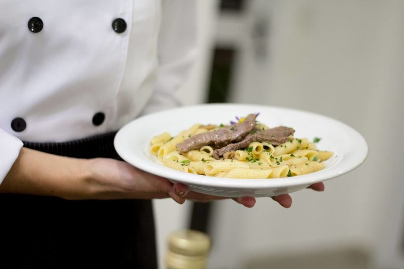 Midsection of female chef holding pasta in kitchen