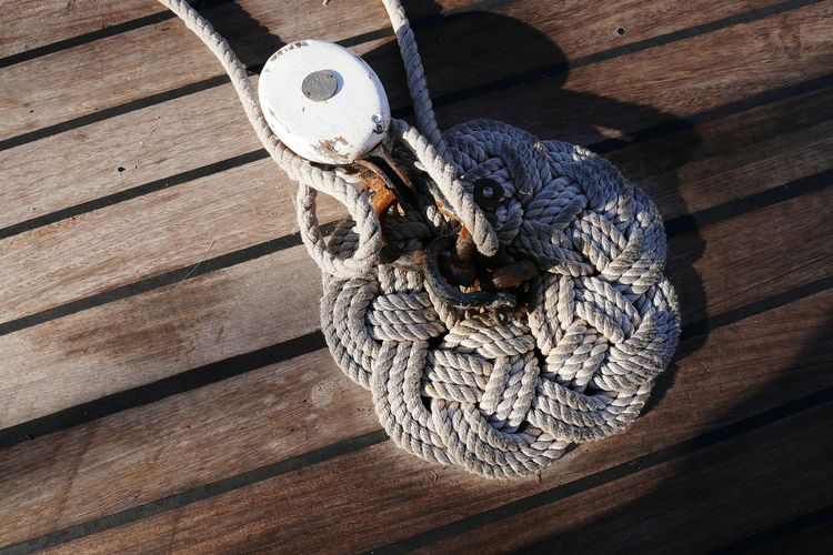 Directly above shot of rope tied to cleat on pier