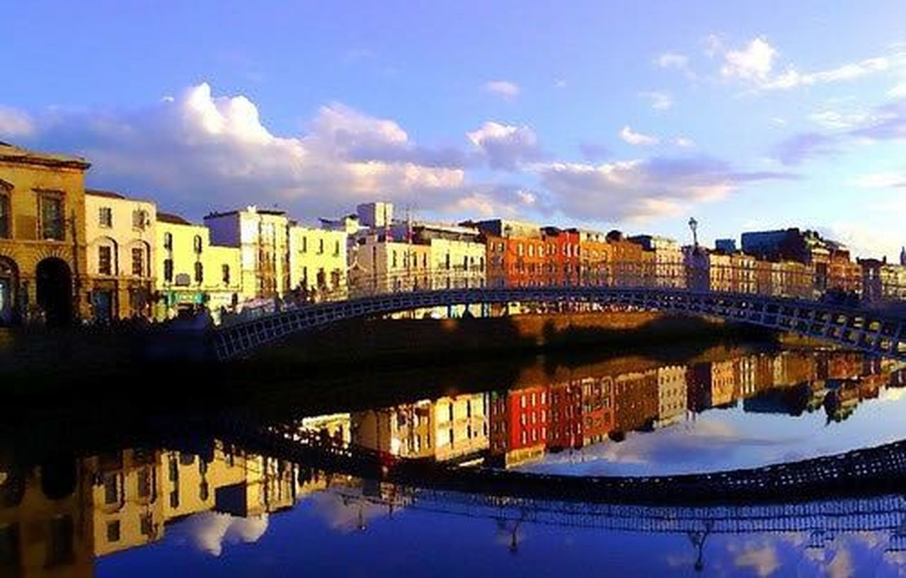 reflection, cloud - sky, sky, river, architecture, water, bridge - man made structure, cityscape, built structure, blue, city, outdoors, building exterior, no people, illuminated, day, urban skyline