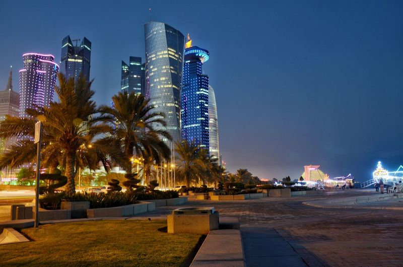 illuminated cityscape of doha qatar. Qatar Doha Landscape Landmark Gulf Middle East Cityscape Illustration Blue Sky City Cityscape Illuminated Skyscraper Tree Neon Nightlife Modern Sky Architecture Office Building Palm Tree Tower Tall Palm Leaf Tall - High Urban Skyline Skyline Clock Tower Communications Tower Palm Frond