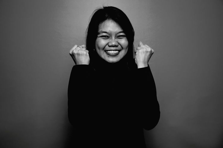 Portrait of a smiling young woman against gray background