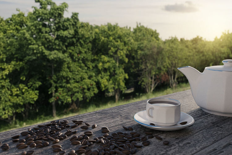 Coffee cup on table against trees