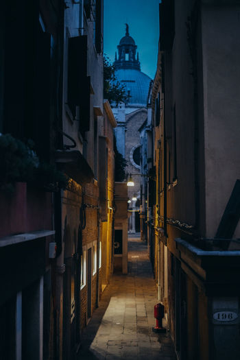 Alley amidst buildings in city at night