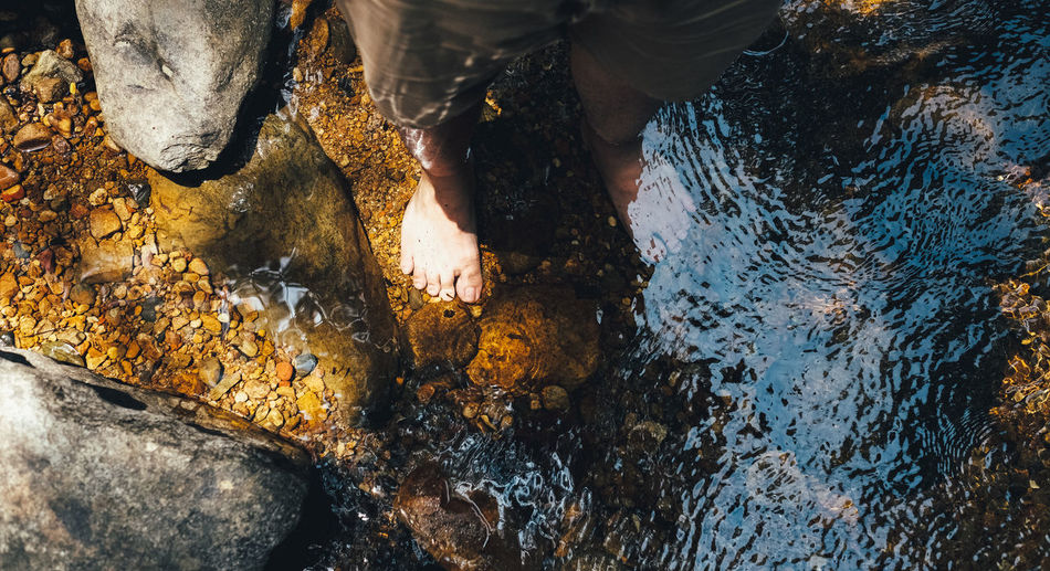 Get Rest Rock Rock - Object Water Solid Low Section High Angle View One Person Nature Human Body Part Day Real People Human Leg Outdoors Hand Unrecognizable Person Sea Wet Human Hand Human Foot Shallow