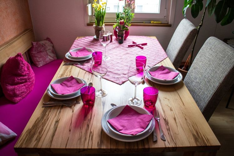View of plates and wine glasses on dining table