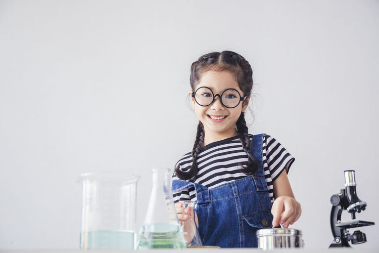 Portrait of smiling girl standing against glass