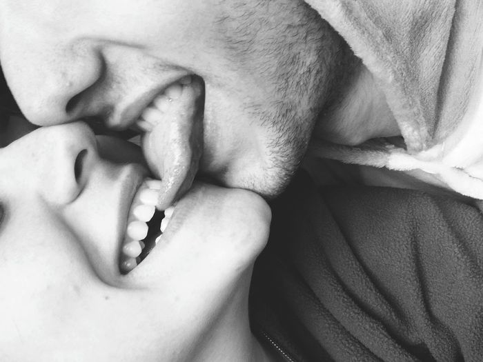 Close-up of smiling young woman biting tongue of boyfriend