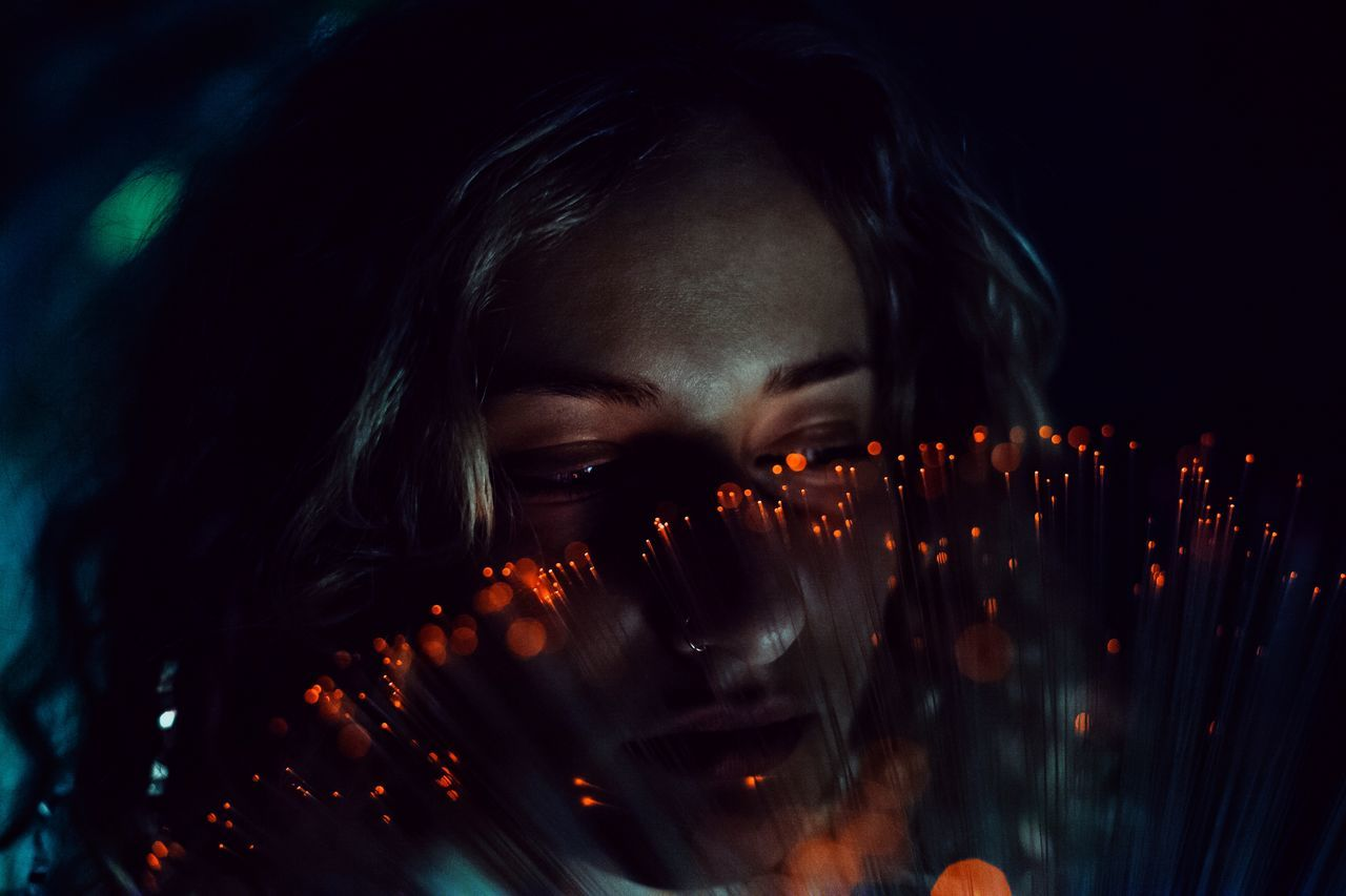 Close-up of thoughtful woman with fiber optic at night