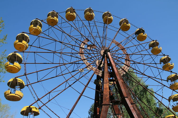 Low angle view of abandoned ferris wheel against clear blue sky