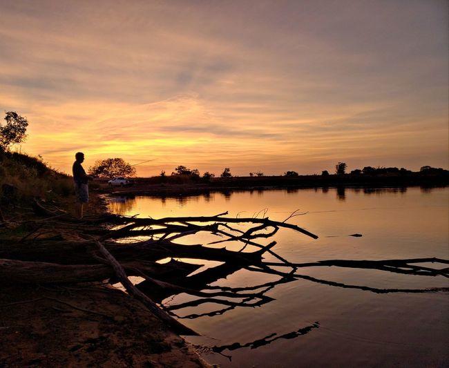 Man standing by lake during sunset