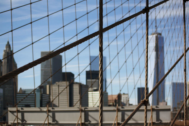 Buildings Seen Through Chainlink Fence Against Sky