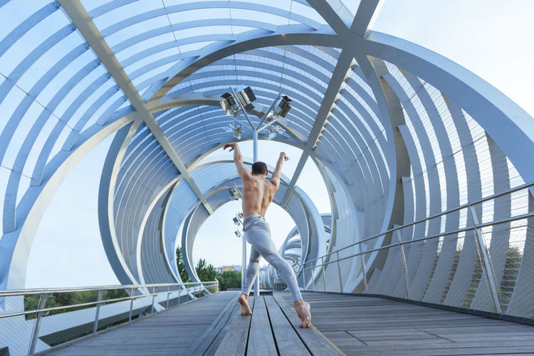 Rear view of shirtless man dancing on bridge