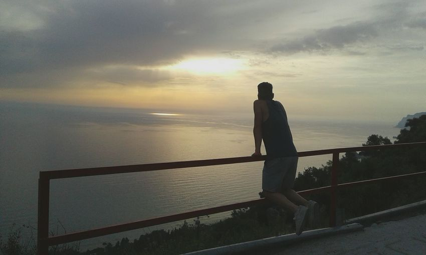 Rear view of man leaning on railing over sea against sky during sunset