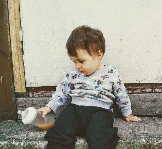 Cute boy holding baby bottle while sitting against closed door