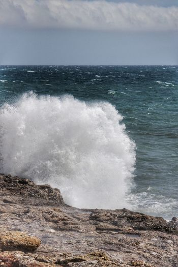 SCENIC VIEW OF SEA SPLASHING ON ROCKS AGAINST CLOUDY SKY