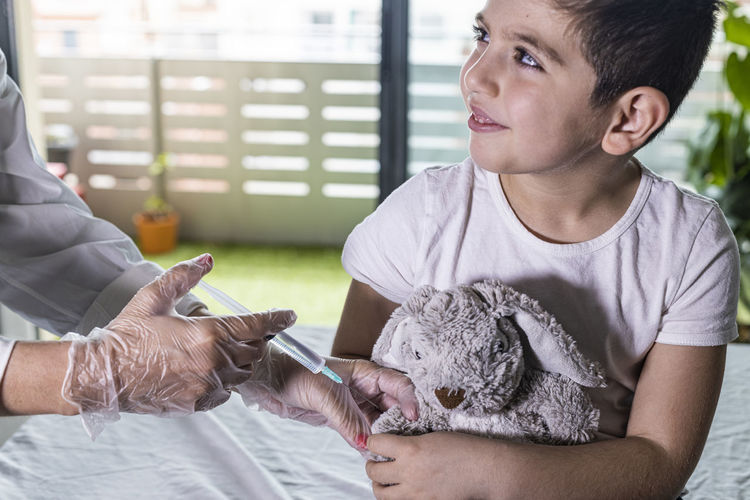 Doctor vaccinating a little boy's teddy bear