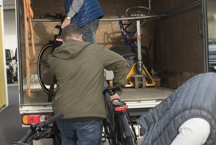 Rear view of man working with bicycle