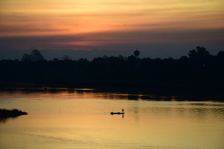 Silhouette trees by lake against orange sky