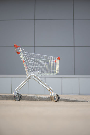 Side view of an abandoned shopping cart against wall