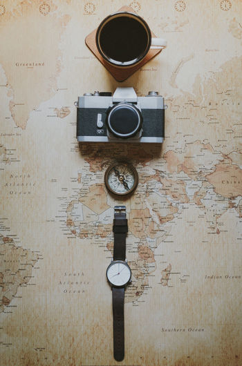 Directly above shot of coffee cup with camera and navigational compass on world map