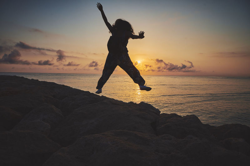 Full length of woman jumping at beach during sunset