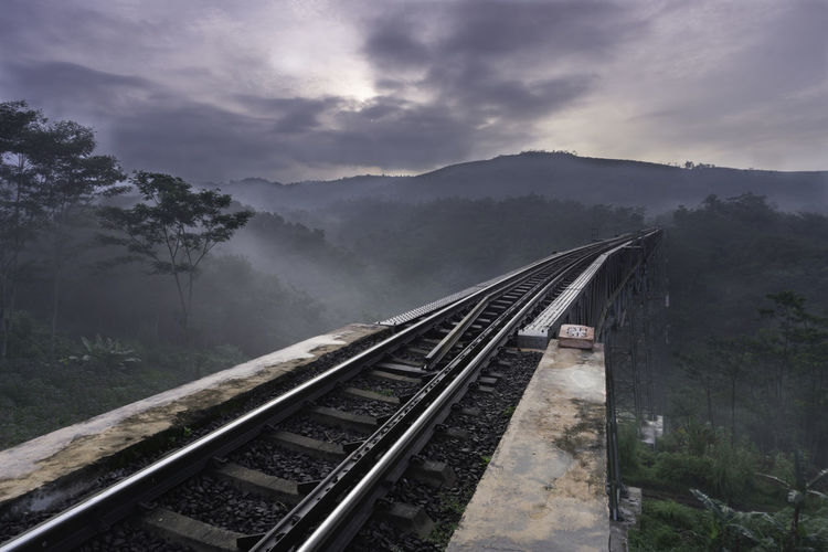 High angle view of railroad tracks against sky, with fog