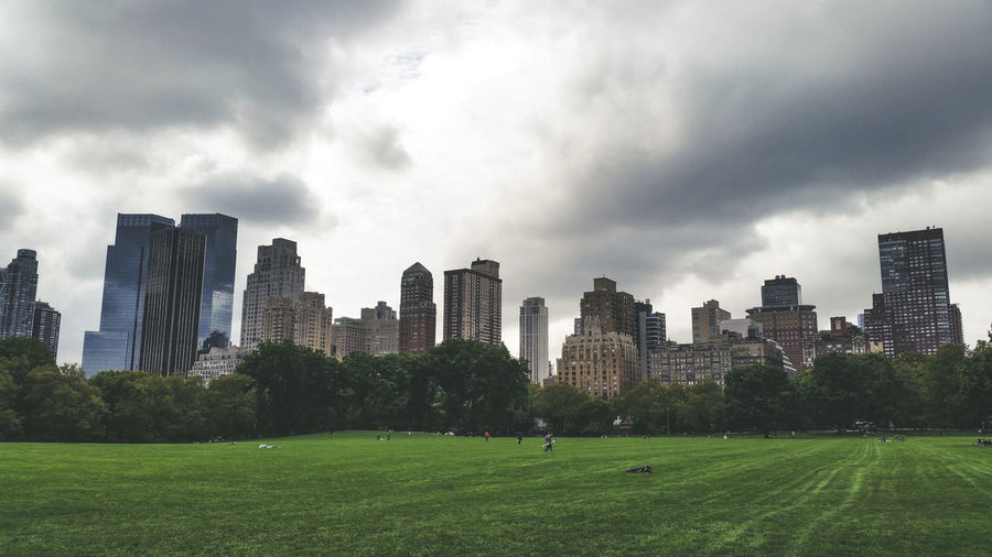 View Of Park In City Against Cloudy Sky
