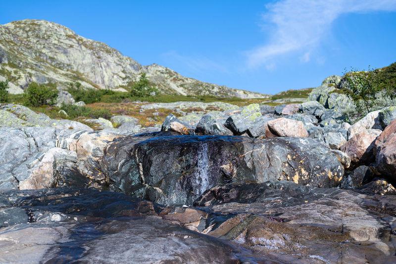 Rocks in water against rock formation