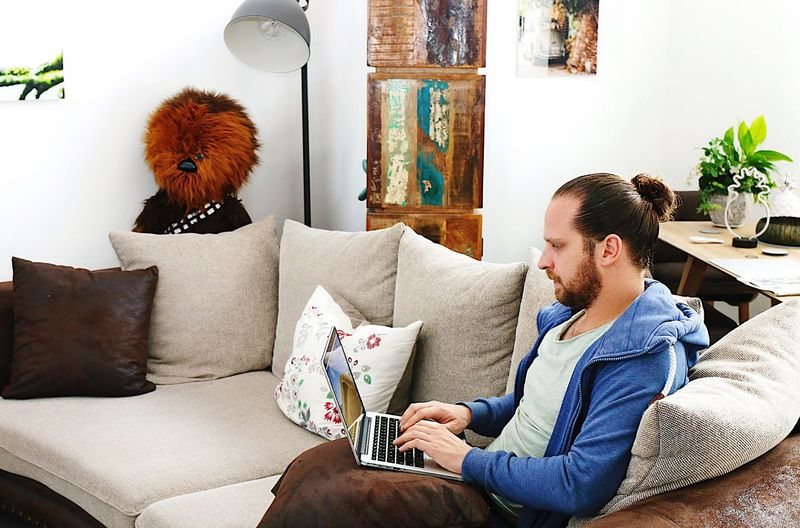 Bearded mid adult man using laptop while sitting on sofa at home