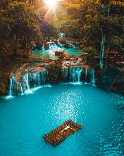 Girl lying on a bamboo raft in the middle if a waterfall in the philippines