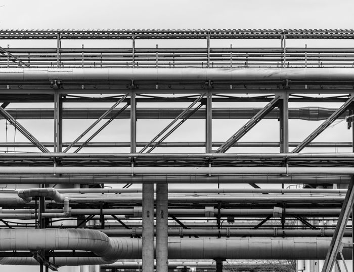 Black And White Production Produce Factory Industry Built Structure Architecture Low Angle View Metal Connection Sky Building Exterior Pipe - Tube No People Day Pipeline Clear Sky Nature Industrial Building  Outdoors Bridge Bridge - Man Made Structure Pattern Complexity Silver Colored Industrial Equipment