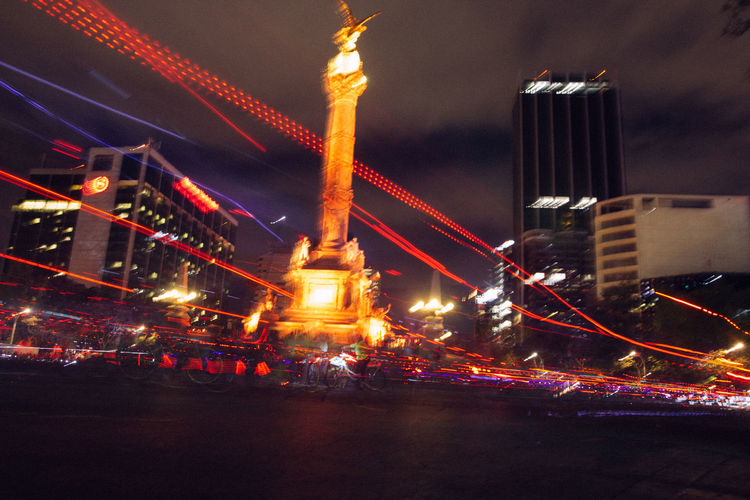 Light trails by monument in city at night