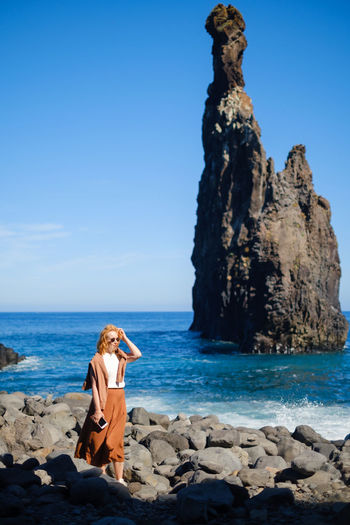 Woman wearing sunglasses standing on beach against rock formation and sky