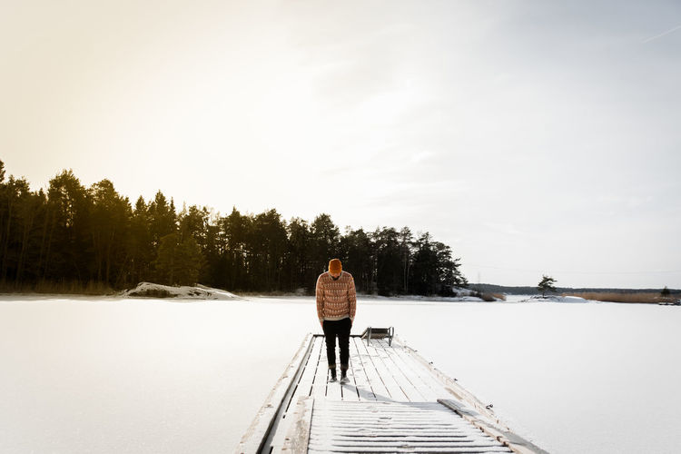 Swedish winter in Trosa. Beauty In Nature Casual Clothing Day Full Length Jetty Lake Leisure Activity Mature Adult Mature Men Men Nature One Man Only One Mature Man Only One Person Only Men Outdoors Pier Real People Rear View Sky Snow Standing Tranquil Scene Winter Wood - Material