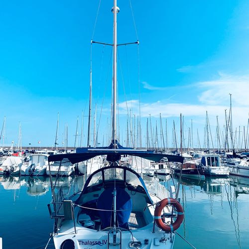 Sailboats moored in harbor against blue sky
