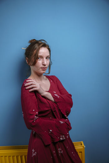Young woman looking away while standing against blue wall