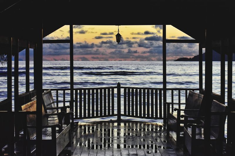 Empty chairs and table by sea against sky seen through window