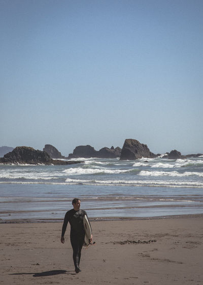 Man With Surfboard Walking At Beach