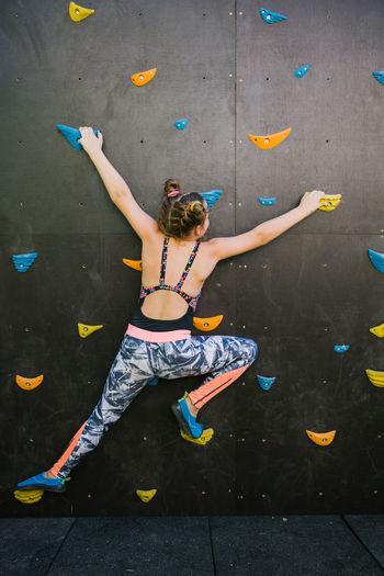 High angle view of woman climbing on wall