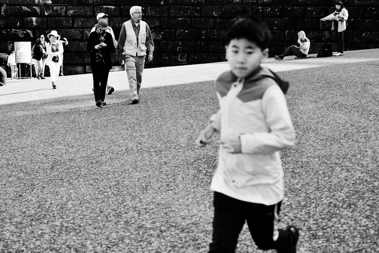 Boy playing with people in background