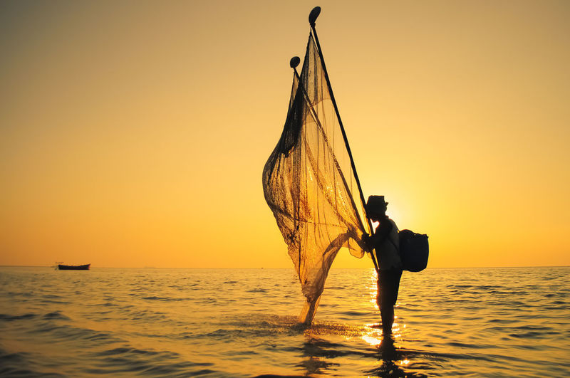 Fisherman With Net Standing In Sea Against Orange Sky During Sunset
