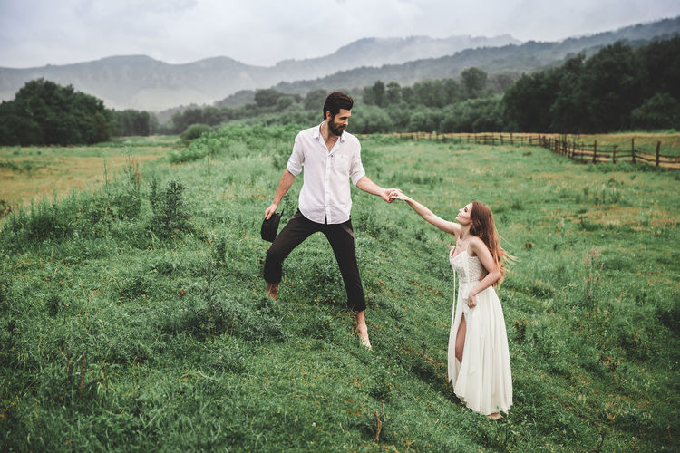 Full length of young couple holding hands while standing on grassy field