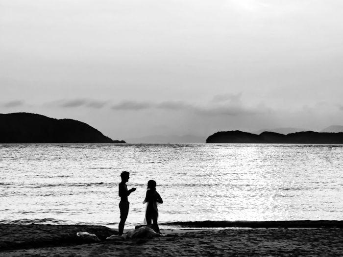 Silhouette women standing on beach against sky