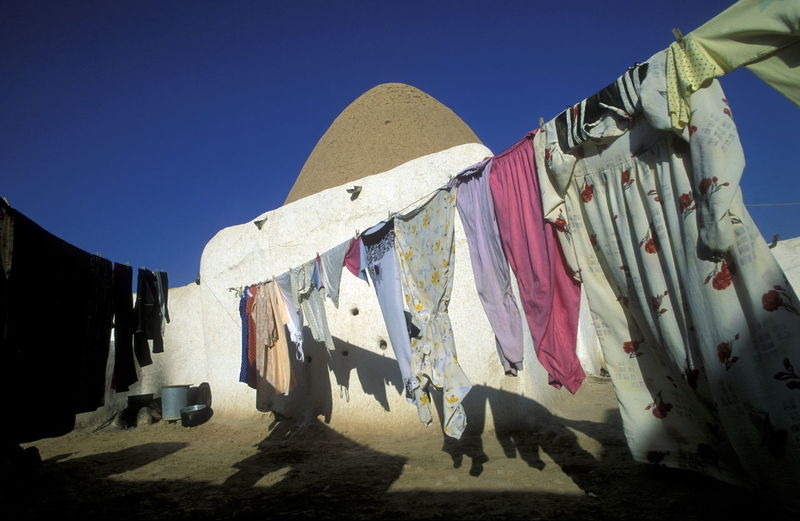 Low Angle View Of Cloths Hanging On Rope Against Clear Blue Sky