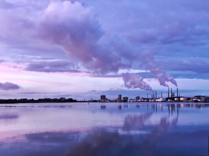 Smoke emitting from factory against sky at dusk