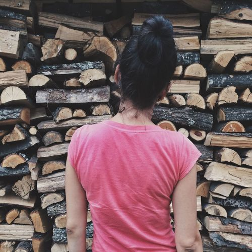 Rear View Of Woman Standing Against Log Stack