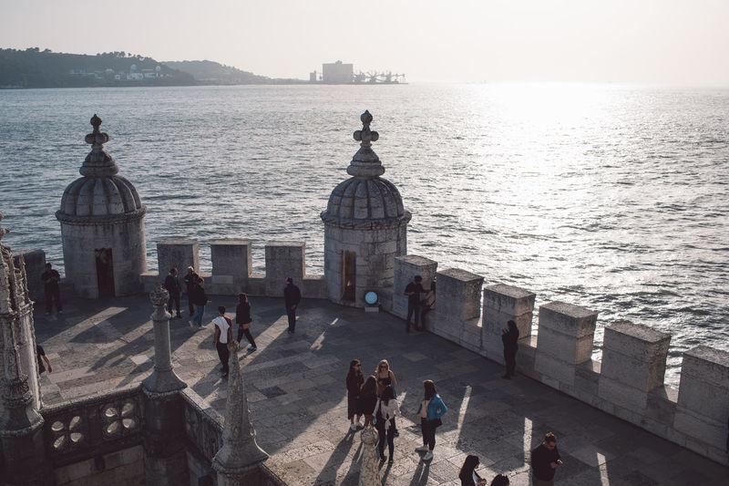 People on bridge over sea in city
